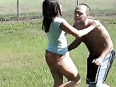Girl kicks and beats on a guy outdoors
